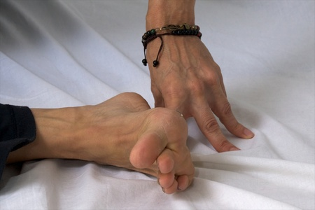 flexed: Close up of hand and foot of woman in studio, foot is flexed and she is pressing fingers into the floor in yoga position