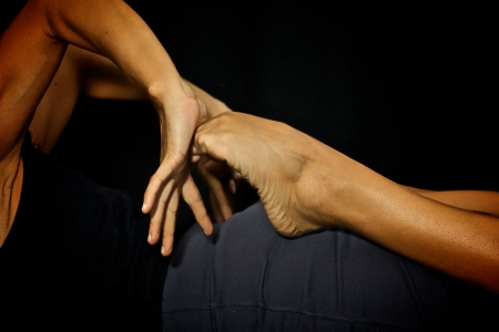 yogini: Close up of woman doing yoga as she presses her palms of her hands against her feet bending the toes on black background.