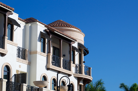 awnings windows: Looking up at balconies and a round room on the outside of an ornate building in tropical florida