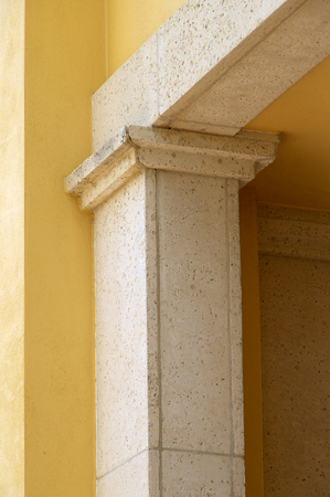 Showing the top of a modern column and portion of wall on exterior of building in Florida