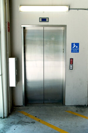 A stainless steel elevator inside a parking garage, the doors are closed. Stockfoto