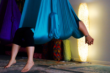 a person is wrapped up and suspended in blue aerial yoga hammock  Banco de Imagens