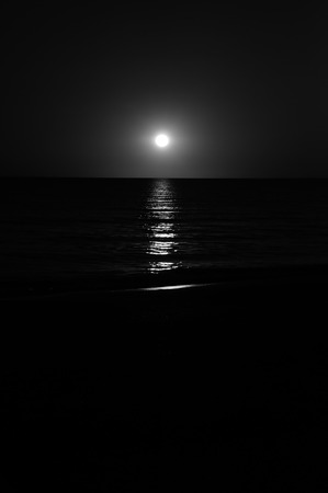 black and white stark image of sunsetting over the sea, with reflections in the waves                           Stock Photo