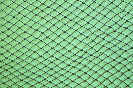 A knotted fishing net is stretched out hanging on a lime green stuccoed wall