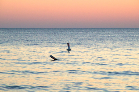 safe water: Two buoys in the water at sunset designate the safe swimming zone in the gulf of mexico in florida Stock Photo