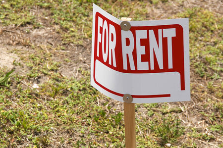 A blank For Rent Sign is screwed to a wooden post and is outside on the lawn