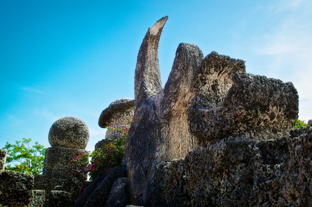 castle rock: Broken and weather carvings sit on top of a wall on the coral castle in tropical florida depicting mars, saturn, and a crescent moon  Stock Photo