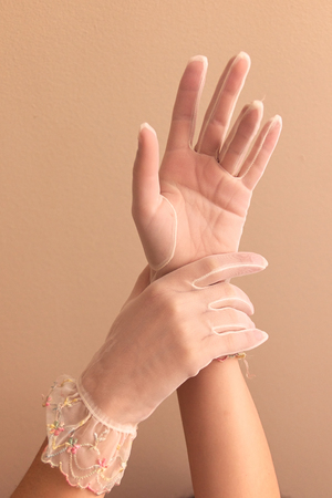 cuffed: Image of womans forearms and hands modeling vintage lace see through gloves.