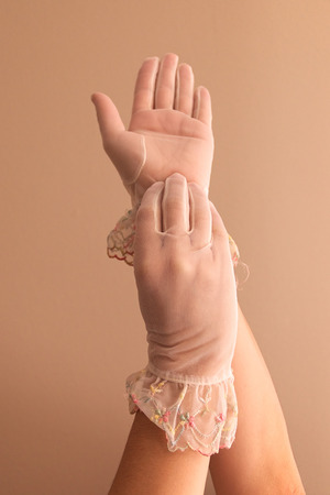 forearms: Image of womans forearms and hands modeling vintage lace see through gloves.