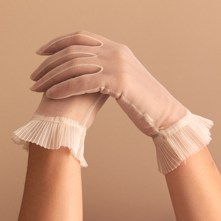 cuffed: Image of womans forearms and hands modeling vintage sheer see through gloves. Stock Photo