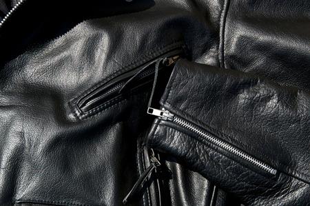 chaqueta de cuero: Contraste de cerca de la chaqueta de cuero de la motocicleta negro que muestra los bolsillos con cremallera y parte de la manga en sol