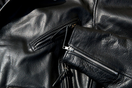 leather jacket: High contrast close up of black leather motorcycle jacket showing zippered pockets and portion of  sleeve in sunshine