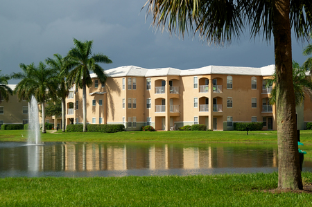 Looking across a pond towards a three story apartment complex in Naples, Florida, with a stormy sky and sunlight on buildings. photo