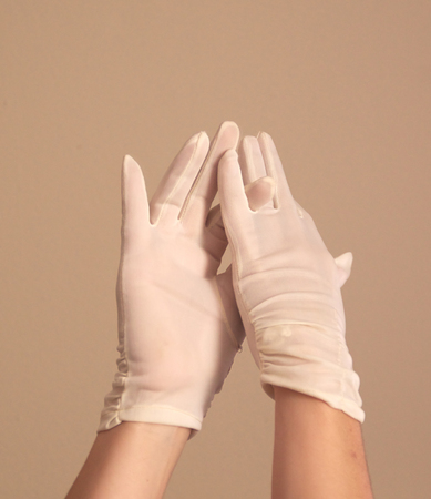 formal dressing: A womans hands and forearms are shown as she models a vintage pair of formal white gloves . She seems to be adjusting the finger length