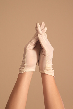 interlaced: A womans hands and forearms are shown as she models a vintage pair of formal white gloves. She She has her fingers crossed and interlaced in steeple shape.