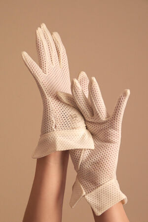 hand cuff: A womans hands and forearms are shown as she models a vintage pair of formal white mesh gloves with unique cuff. She is using one hand to pull on the other glove. Stock Photo