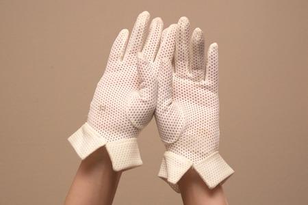 cuffed: Las manos y los antebrazos de una mujer como ella se muestran los modelos de un par de �poca de malla formales guantes blancos con manguito �nico. Ambas palmas se enfrentan al espectador.