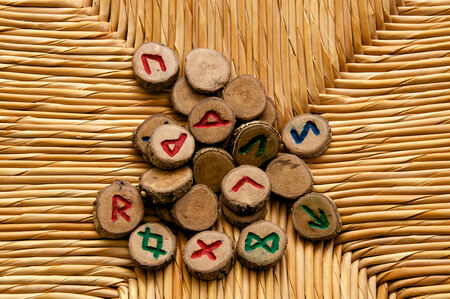 futhark: Looking own on a pile of germanic runes, an ancient alphabet known as the futhark on a woven rattan surface. Note: These runes were made by the photographer.