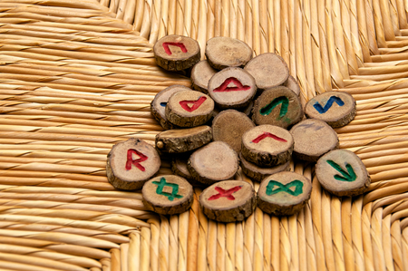 futhark: A pile of germanic runes, an ancient alphabet known as the futhark are on a woven rattan surface. Note: These runes were made by the photographer.