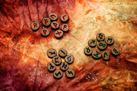 futhark: set of wooden runes, an ancient alphabet known as the futhark are divided into the three aetts, on a colorful hand dyed fabric with small sparkling beads.