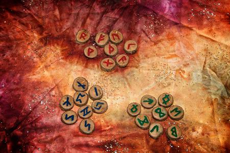 tres conjuntos de runas de madera, un antiguo alfabeto conocido como el futhark están en una tela teñida a mano colorido con pequeñas cuentas brillantes. Foto de archivo