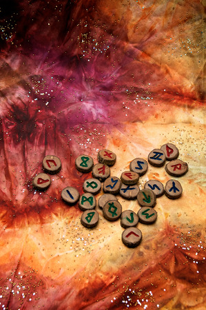 hand carved and painted wooden runes, an ancient alphabet known as the futhark are on a colorful hand dyed fabric with small sparkling beads. photo