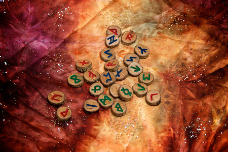 futhark: hand carved and painted wooden runes, an ancient alphabet known as the futhark, are on a colorful hand dyed fabric with small sparkling beads.