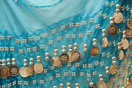 silvery: A blue antique belly dancers skirt showing silvery beads and charms.