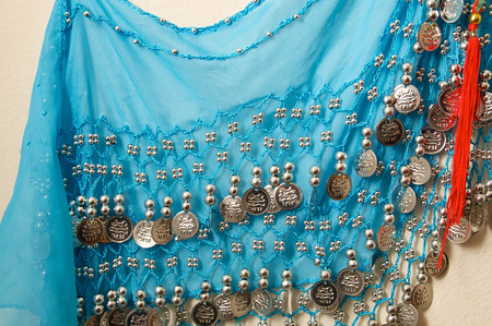 silvery: A blue vintage belly dancers skirt hanging on wall showing silvery beads and charms with red tassel.