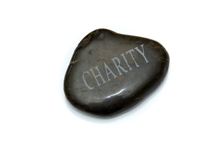 smooth: A smooth polished stone with the word Charity engraved in the top of it. Over white.