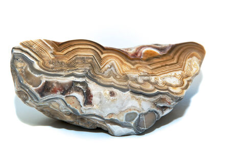 greys: A layers and colorful cut and polished stone over white showing the various designs within. Over white. Stock Photo