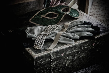 A grainy desaturated fine art still life image of womans various theater props and costume parts. Stock Photo