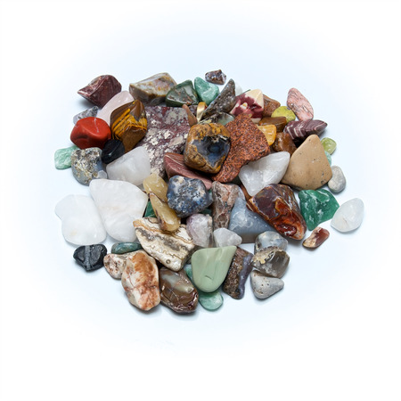 tumbled stones: A pile of many different size, shape and colored tumbled stones, shot over white surface. Stock Photo