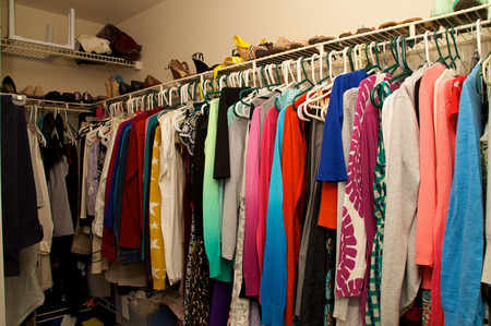 walk in closet: closet belonging to a woman. Full of clothing, hangers, shelves and shoes. Stock Photo