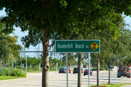 rd: A green Vanderbilt Beach Rd sign on Livingston Road in Naples florida with morning traffic. Stock Photo