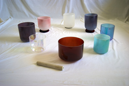 A collection of colorful crystal singing bowls against white backdrop. Imagens