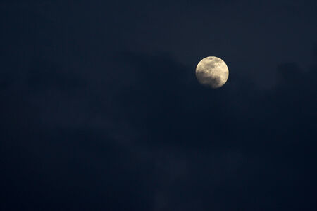 A night sky with clouds obscuring part of the full moon.