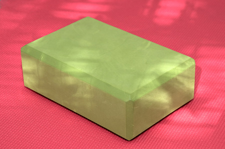 A green yoga block on a pink yoga mat with dappled sunlight adding depth and texture to the image.