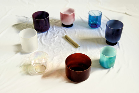 A collection of colorful crystal singing bowls against white backdrop. Stock Photo