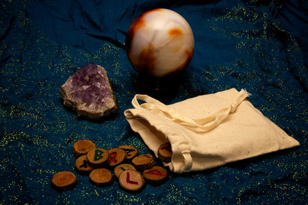 muslin: A plain muslin bag with wooden runes spilling out over a sparkling blue cloth with amethyst and crystal ball in the background.