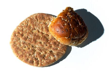 Een klein brood van meergranen plat brood en een meergranen broodje van bovenaf op wit. Verlicht vanaf de zijkant om textuur te tonen. Stockfoto