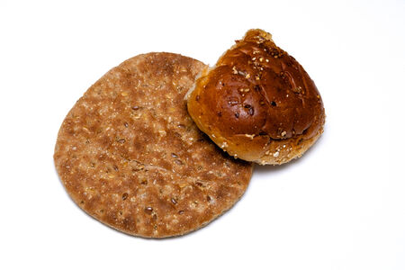 A small loaf of multigrain flat bread and a multigrain roll from above on white.