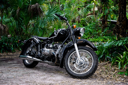 A vintage black motorcycle with tank shifter sits on a path in a tropical setting