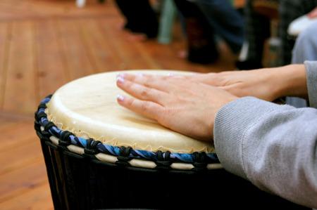 tambor: Feche acima das m�os da mulher enquanto ela tambores em um c�rculo de tambores.