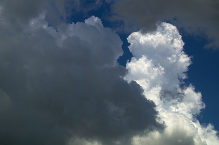 Storm clouds gathering at midday against a blue sky.