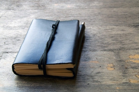 old diary: A leather bound journal sits on a table outside with a cord wrapped around the pages to keep place in book. Stock Photo