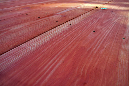 Looking down the length of a red stained wooden picnic table in perspective.
