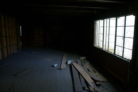 Looking down the length of an old abandoned house towards a fireplace with only sunlight coming in from the side.