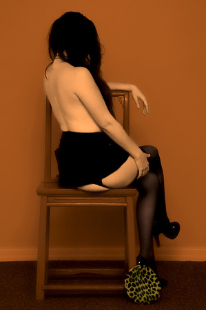 A long haired caucasian woman is sitting topless facing away from the viewer in this hand tinted image. photo