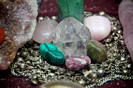 alter: A quartz crystal is surrounded by various polished stones which is in turn encircled with silver chains on alter.